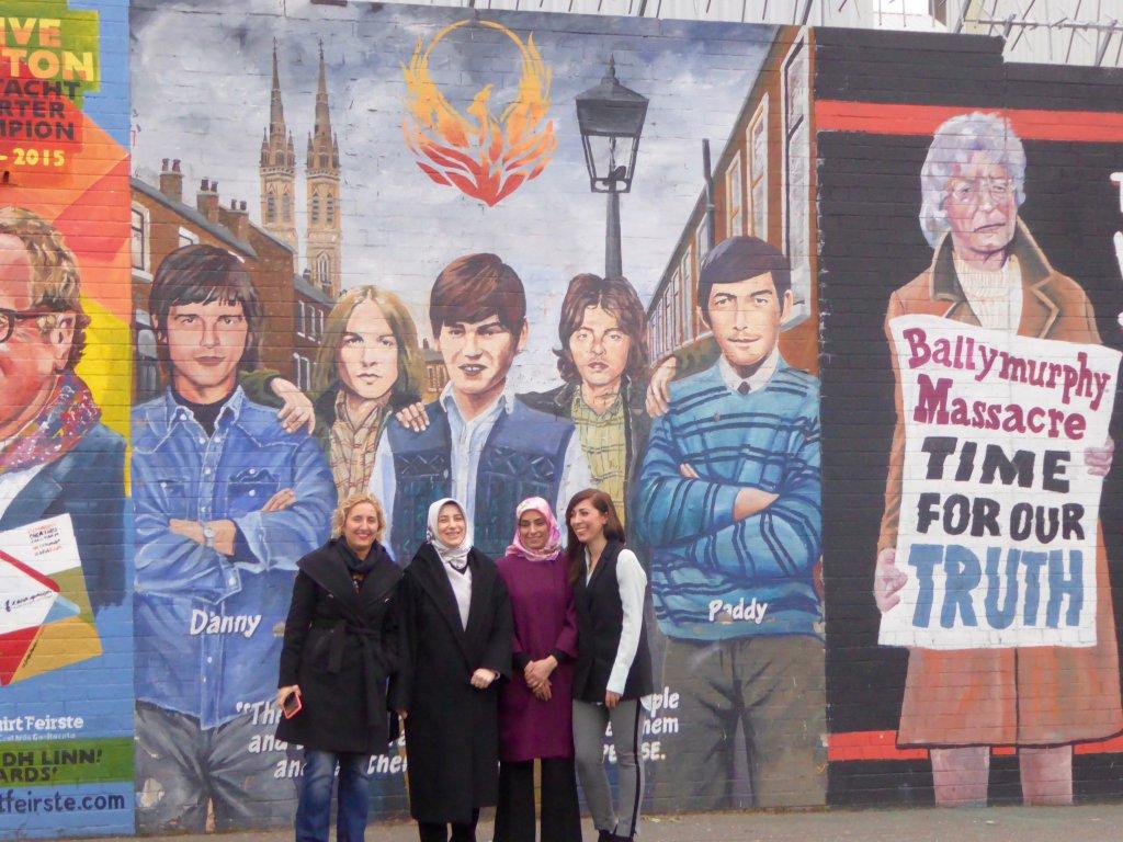 DPI Participants Melda Onur, Özlem Zengin, Zehra Taşkesenlioğlu and Nurcan Baysal stand in front of murals on the Falls Road.