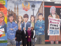 DPI Participants Melda Onur, Özlem Zengin, Zehra Taşkesenlioğlu and Nurcan Baysal stand in front of murals on the Falls Road.